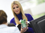 President Donald Trump's daughter Ivanka Trump holds a training circuit board during a tour of Lockheed Martin in Littleton, Colo., Monday, July 22, 2019. (RJ Sangosti/The Denver Post via AP)