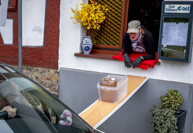 A can with apple cider slides down to car from a window of the apple cider restaurant 'Zum Lahmen Esel' in Frankfurt, Germany, Friday, April 3, 2020. Due to the coronavirus outbreak the restaurant which has been in operation since 1807 offers cider and food to go in a self-made drive through set up. (AP Photo/Michael Probst)