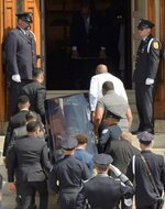 """Pallbearers carry the casked of Worcester Police Officer Enmanuel """"Manny"""" Familia into St. John's Catholic Church for a funeral Mass, Thursday, June 10, 2021, in Worcester, Mass. Familia, 38, died Friday, June 4, trying to save 14-year-old Troy Love, who had fallen into a pond. Love also died. (Rick Cinclair/Worcester Telegram & Gazette via AP)"""