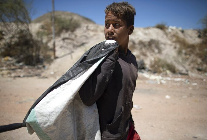 Ronaikel Brito walks home with a sack of things he collected from the Pavia garbage dump that he can sell, on the outskirts of in Barquisimeto, Venezuela, Wednesday, March 3, 2021. The 16-year-old began helping his mother Marbelis sift through garbage when he was five years old, following in the steps of his grandmother. (AP Photo/Ariana Cubillos)