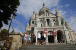Tourists stroll by the Sacre Coeur basilica in the Montmartre district Monday, Aug. 10, 2020 in Paris. People are required to wear a mask outdoors starting on Monday in the most frequented areas of the French capital. The move comes as the country sees an uptick in virus infections. (AP Photo/Michel Euler)