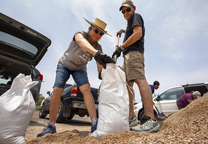 Julia Andres, left, and her husband David Andres fill sand bags for their home at Hi Corbett Field parking lot in Tucson, Ariz., Thursday, July 22, 2021. The City of Tucson was offering free self-serve sand bags at numerous vacations in advance of a forecast of heavy rain. (Rebecca Sasnett/Arizona Daily Star via AP)
