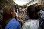 Lilian Tintori, center, wife of opposition leader Leopoldo Lopez speaks with relatives of prisoners, outside of Venezuelan political police headquarters, SEBIN, in Caracas, Venezuela, Wednesday, May 16, 2018. In two short videos shot on a cell phone and posted Wednesday on his Facebook page U.S jailed ctizen Joshua Holt said his life was threatened during a disturbance by inmates that include President Nicolas Maduro's top opponents. Venezuela's chief prosecutor sent a commission to the jail to discuss the prisoners' demands. (AP Photo/Fernando Llano)