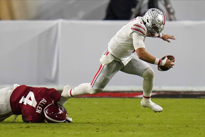 Ohio State quarterback Justin Fields is tackled by Alabama linebacker Christopher Allen during the first half of an NCAA College Football Playoff national championship game, Monday, Jan. 11, 2021, in Miami Gardens, Fla. (AP Photo/Chris O'Meara)