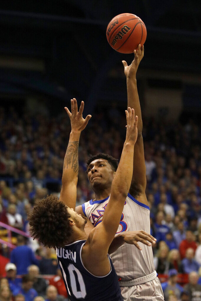 Kansas forward David McCormack, right, shoots over Monmouth forward Jarvis Vaughan (10) during the first half of an NCAA college basketball game in Lawrence, Kan., Friday, Nov. 15, 2019. (AP Photo/Orlin Wagner)