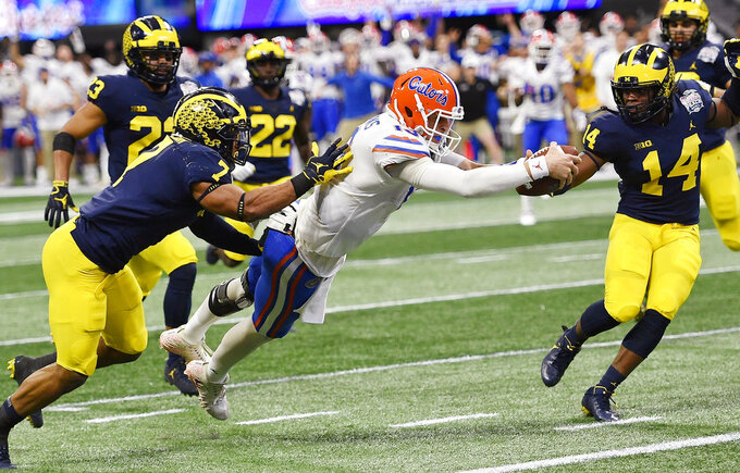 Florida quarterback Feleipe Franks (13) leaps into the end zone for a touchdown against Michigan linebacker Khaleke Hudson (7) during the first half of the Peach Bowl NCAA college football game, Saturday, Dec. 29, 2018, in Atlanta. (AP Photo/Mike Stewart)