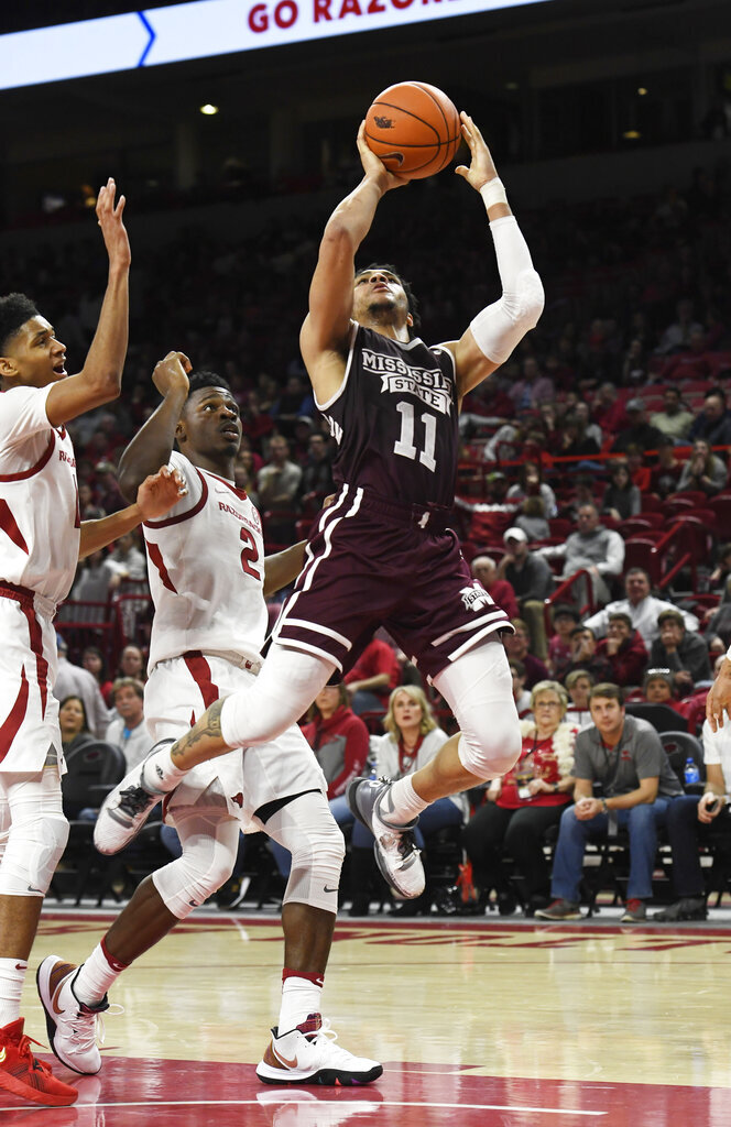 Mississippi State guard Quinndary Weatherspoon (11) drives past Arkansas defenders Isaiah Joe and Adrio Bailey (2) during the second half of an NCAA college basketball game Saturday, Feb. 16, 2019, in Fayetteville, Ark. (AP Photo/Michael Woods)