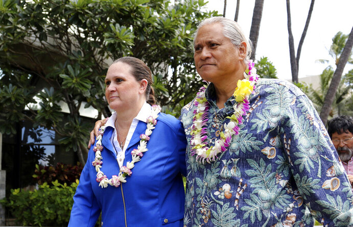 FILE - In this Oct. 20, 2017, file photo, former Honolulu Police Chief Louis Kealoha, right, and his wife, Katherine, leave federal court in Honolulu. Court records show Louis Kealoha filed for divorce Tuesday, Oct. 15, 2019. A jury in June convicted him and Katherine Kealoha of conspiracy in a plot to frame her uncle to keep him from revealing fraud that financed their lavish lifestyle. The Kealohas are facing another trial for bank fraud and identity theft.  (AP Photo/Caleb Jones, File)