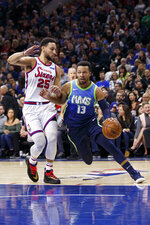 Dallas Mavericks' Jalen Brunson, right, drives to the basket against Philadelphia 76ers' Ben Simmons, left, during the first half of an NBA basketball game, Friday, Dec. 20, 2019, in Philadelphia. (AP Photo/Chris Szagola)