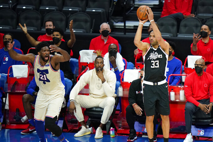 Los Angeles Clippers' Nicolas Batum (33) goes up for a shot past Philadelphia 76ers' Joel Embiid (21) during the second half of an NBA basketball game, Friday, April 16, 2021, in Philadelphia. (AP Photo/Matt Slocum)
