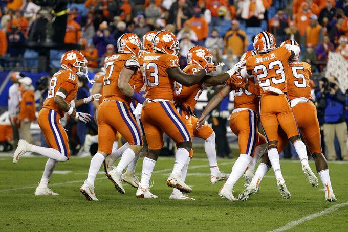 Clemson players celebrate towrds the end of the second half of the Atlantic Coast Conference championship NCAA college football game against Virginia in Charlotte, N.C., Saturday, Dec. 7, 2019. Clemson won 62-17. (AP Photo/Gerry Broome)