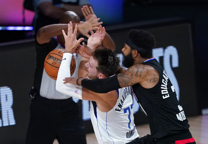 FILE - In this Aug. 30, 2020, file photo, Dallas Mavericks' Luka Doncic (77) is fouled by Los Angeles Clippers' Marcus Morris Sr. during the first half of an NBA basketball first-round playoff game in Lake Buena Vista, Fla. Doncic's first experience with the playoffs ended with questions about whether Morris was intentionally trying to hurt the young Dallas sensation in a first-round series won by LA. The Mavericks might have hinted at what they thought through trades and draft picks during this abbreviated offseason. Dallas acquired James Johnson and his black belt in karate from the Oklahoma City Thunder after using the club's first-round choice at No. 18 overall on Josh Green, who was a strong defender in his only season at Arizona. (AP Photo/Ashley Landis, File)