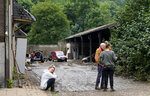 A woman sits in front of her damaged house after flooding in Pepinster, Belgium, Saturday, July 17, 2021. Residents in several provinces were cleaning up after severe flooding in Germany and Belgium turned streams and streets into raging torrents that swept away cars and caused houses to collapse. (AP Photo/Virginia Mayo)