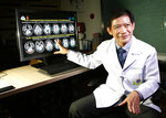 In this Wednesday, Nov. 14, 2018, photo, Dr. Witaya Sungkarat, Ramathibodi Hospital, explains brain scans from young boxers.Witaya said studies show that the sport caused damages, and in many cases, irreparable, in the young children's brain development. Thai lawmakers recently suggested barring children younger than 12 from competitive boxing, but boxing enthusiasts strongly oppose the change. (AP Photo/Sakchai Lalit)
