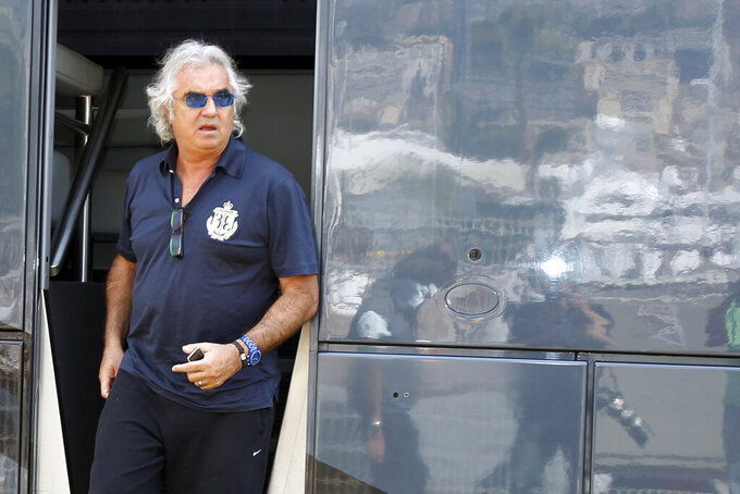 FILE - In this May 14, 2010 file photo, former Renault Team principal Flavio Briatore leaves the FIA motorhome ahead of the Monaco Formula One Grand Prix at the Monaco racetrack, in Monaco. On Tuesday Aug. 25, 2020, Briatore has reportedly been admitted to hospital in Milan with coronavirus, there has been no official statement from the hospital but multiple reports say Briatore's condition is serious but he is not in intensive care.  (AP Photo/Luca Bruno, file)