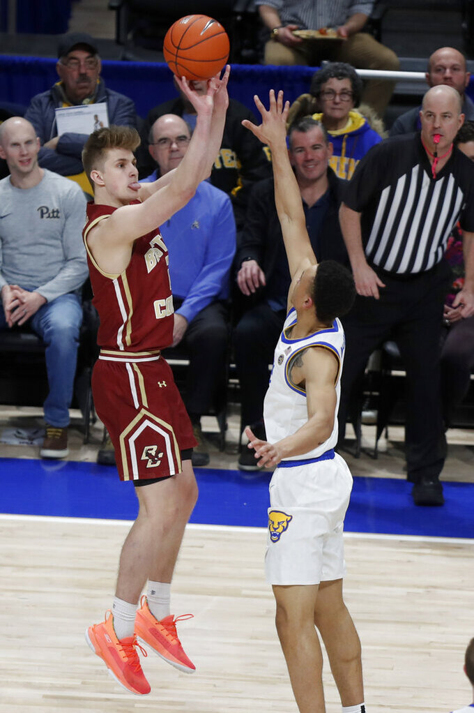 Boston College's Julian Rishwain, left, hits a three-point shot over Pittsburgh's Trey McGowens during the first half of an NCAA college basketball game, Wednesday, Jan. 22, 2020, in Pittsburgh. (AP Photo/Keith Srakocic)
