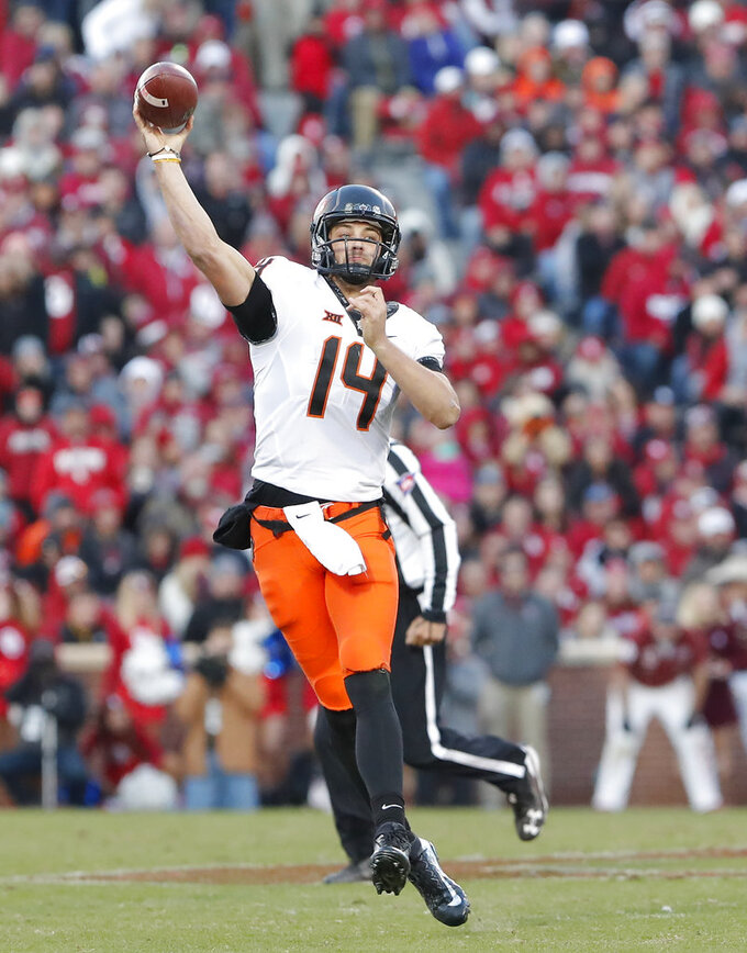 Oklahoma State quarterback Taylor Cornelius (14) throws against Oklahoma in the second half of an NCAA college football game in Norman, Okla., Saturday, Nov. 10, 2018. Oklahoma won 48-47. (AP Photo/Alonzo Adams)
