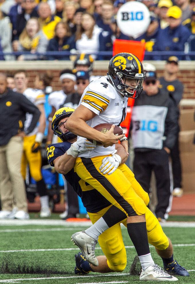 Michigan linebacker Jordan Glasgow, left, sacks Iowa quarterback Nate Stanley (4) in the fourth quarter of an NCAA college football game in Ann Arbor, Mich., Saturday, Oct. 5, 2019. Michigan won 10-3. (AP Photo/Tony Ding)