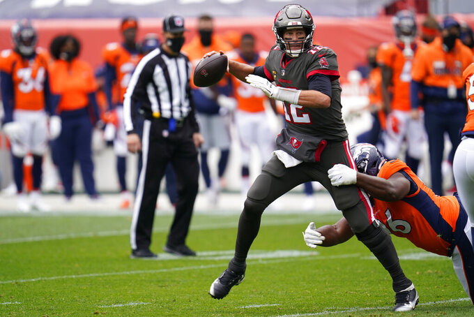 Tampa Bay Buccaneers quarterback Tom Brady throws a pass under pressure from Denver Broncos defensive end Shelby Harris, right, during the first half of an NFL football game Sunday, Sept. 27, 2020, in Denver. (AP Photo/David Zalubowski)