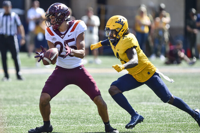 Virginia Tech Keleb Smith makes a catch before he is tackled by West Virginia safety Alonzo Addae (4) during the second half of an NCAA college football game in Morgantown, W.Va., Saturday, Sep. 18, 2021. (AP Photo/William Wotring)