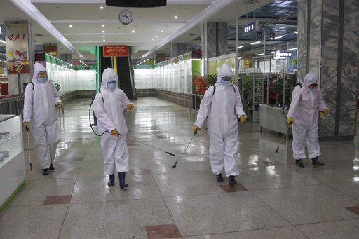 FILE - In this Dec. 28, 2020, file photo, staff of the Pyongyang Department Store No. 1 disinfect the store to help curb the spread of the coronavirus before it opens in Pyongyang, North Korea. The World Health Organization says it has started a process of sending COVID-19 medical supplies to North Korea through the Chinese port of Dalian, a possible sign that the North is easing one of the world's toughest pandemic border closures to receive outside help.(AP Photo/Jon Chol Jin, File)