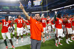 Miami head coach Manny Diaz, center, celebrates with the team after they defeated Bethune-Cookman in an NCAA college football game Saturday, Sept. 14, 2019, in Miami Gardens, Fla. Miami. (AP Photo/Wilfredo Lee)