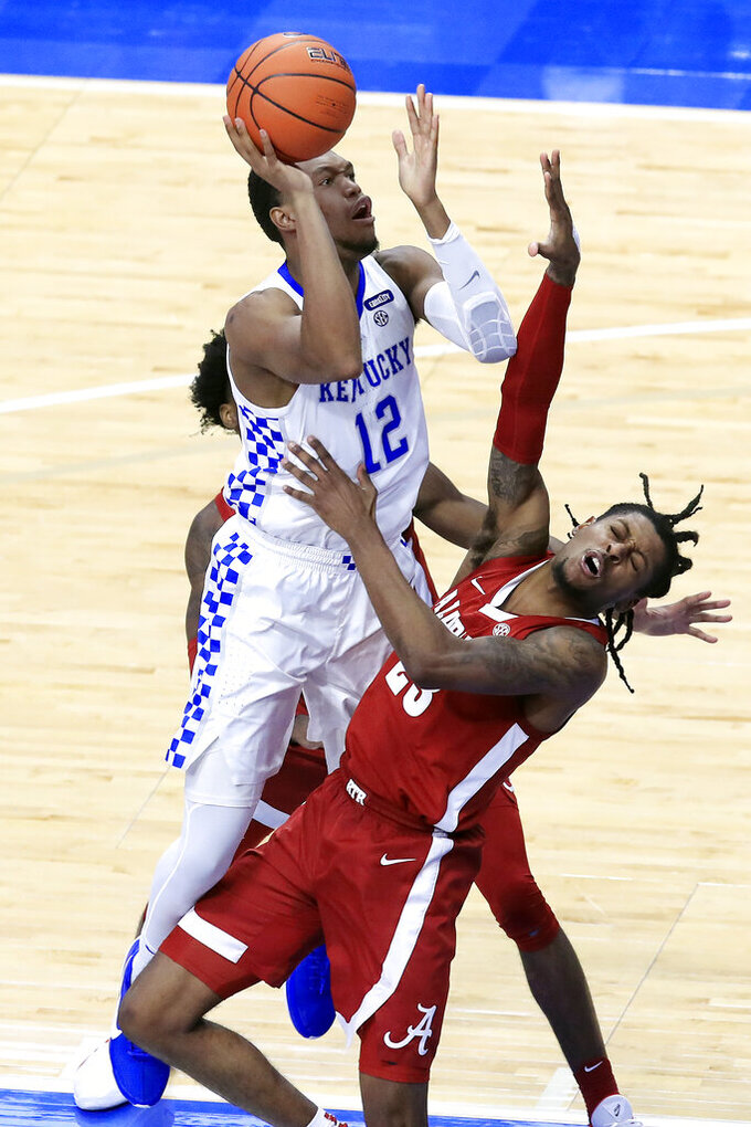 Kentucky's Keion Brooks Jr. (12) shoots while guarded by Alabama's John Petty Jr., right, during the second half of an NCAA college basketball game in Lexington, Ky., Tuesday, Jan. 12, 2021. (AP Photo/James Crisp)