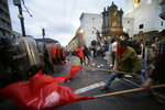 Protesters clash with police blocking them from advancing closer to the presidential palace in Quito, Ecuador, Tuesday, April 16, 2019. Protesters were demonstrating against the policies of President Lenin Moreno's government, including the recent firing of state workers, the taking of an IMF loan and the removal of Julian Assange's asylum status. (AP Photo/Dolores Ochoa)