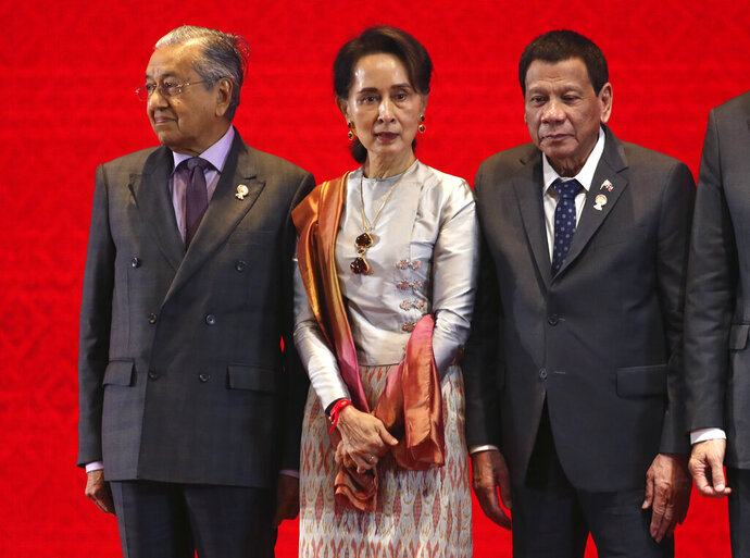Myanmar leader Aung San Suu Kyi, center, stands with Malaysian Prime Minister Mahathir Mohamad, left, and Philippines' President Rodrigo Duterte during the opening ceremony of The Association of Southeast Asian Nations (ASEAN) summit in Nonthaburi, Thailand, Sunday, Nov. 3, 2019. (AP Photo/Aijaz Rahi)