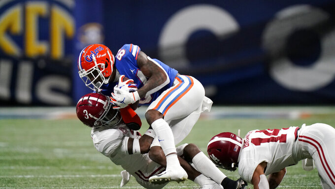 Florida tight end Kyle Pitts (84) is hit by Alabama defensive back Daniel Wright (3) during the first half of the Southeastern Conference championship NCAA college football game, Saturday, Dec. 19, 2020, in Atlanta. (AP Photo/Brynn Anderson)