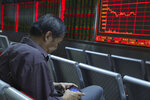 In this Wednesday, Sept. 25, 2019, photo, a Chinese man plays a game on his mobile phone as he monitors stock prices at a brokerage in Beijing. Asian stock markets followed Wall Street higher Thursday, Sept. 26, 2019, after U.S. President Donald Trump suggested a costly tariff war with China could be resolved soon. (AP Photo/Ng Han Guan)