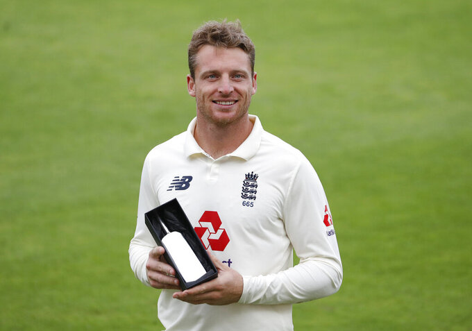 FILE - In this file photo dated Tuesday, Aug. 25, 2020, England's Jos Buttler poses with England's Man of the Series award on the fifth day of the third cricket Test match between England and Pakistan, at the Ageas Bowl in Southampton, England.  England's cricketers are flying to South Africa it is announced Monday Nov. 16, 2020, on the back of reassurances from team management that the white-ball tour will take place as scheduled, although England star Jos Buttler said CSA's issues had led to him fearing the tour might be canceled.(AP Photo/Alastair Grant, FILE)