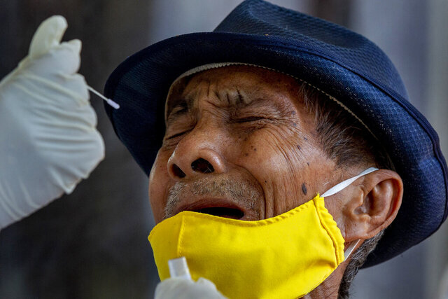 A man grimaces as a nasal swab sample is collected from him to test for a new coronavirus in Bangkok, Thailand, Wednesday, May 6, 2020. Thai health workers started testing community of about 1,600 people of Klong Toey slum at a nearby Buddhist temple. (AP Photo/Gemunu Amarasinghe)