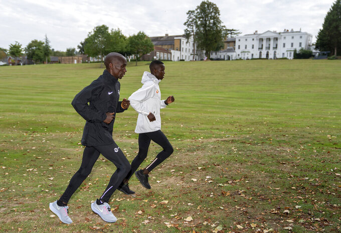 In this image issued by London Marathon Events, Kenya's Eliud Kipchoge trains alongside his pacemaker in the grounds of the official hotel and biosecure bubble in London, Monday Sept. 28, 2020, ahead of the elite-only 2020 London Marathon on Sunday Oct. 4. The 40th Race will take place on a closed-loop circuit around St James's Park in central London. (Bob Martin/London Marathon Events via AP)