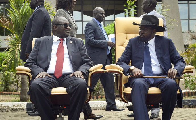FILE - In this Friday, April 29, 2016 file photo, South Sudan's then First Vice President Riek Machar, left, looks across at President Salva Kiir, right, as the two sit to be photographed following the first meeting of a new transitional coalition government, in the capital Juba, South Sudan. South Sudan's warring parties on Wednesday, Sept. 12, 2018, signed what they say is the final peace agreement to end the country's five-year civil war, which has killed tens of thousands and displaced millions. (AP Photo/Jason Patinkin, File)