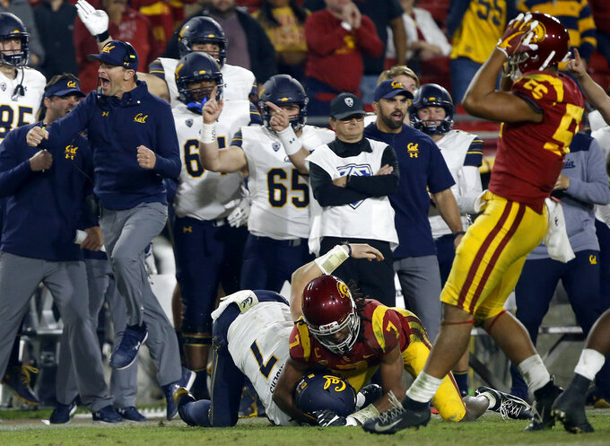 California head coach Justin Wilcox, left, leaps to celebrate a first down by quarterback Chase Garbers, center, by Southern California safety Marvell Tell III, second from right, as linebacker Jordan Iosefa, right, laments during the second half of an NCAA college football game in Los Angeles, Saturday, Nov. 10, 2018. California won 15-14. (AP Photo/Alex Gallardo)