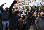 People protest restrictions imposed by authorities due to the pandemic in the Rastro flea market in Madrid, Spain, Sunday, Nov. 22, 2020. Madrid's ancient and emblematic Rastro flea market reopened Sunday after a contentious eight-month closure because of the COVID-19 pandemic that has walloped the Spanish capital. (AP Photo/Paul White)