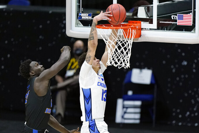 Creighton's Christian Bishop (13) scores ahead of UC Santa Barbara's Amadou Sow, left, during the first half of a college basketball game in the first round of the NCAA tournament at Lucas Oil Stadium in Indianapolis Saturday, March 20, 2021. (AP Photo/Mark Humphrey)