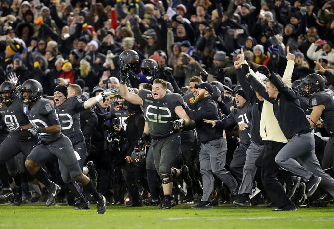 FILE - In this Dec. 10, 2016, file photo, Army players and coaches run onto the field after defeating Navy 21-17 in an NCAA college football game in Baltimore, Md. With Army ranked No. 22, the Cadets (9-2) try to beat Navy (3-9) for the third straight time Saturday, Dec. 8, 2018, in the storied series. (AP Photo/Patrick Semansky, File)