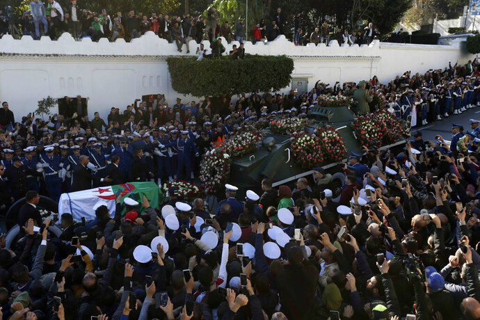 People gather during the funeral Gen. Ahmed Gaid Salah,  in Algiers, Algeria, Wednesday, Dec. 25, 2019. Algeria is holding an elaborate military funeral for the general who was the de facto ruler of the gas-rich country amid political turmoil throughout this year. (AP Photo/Toufik Doudou)