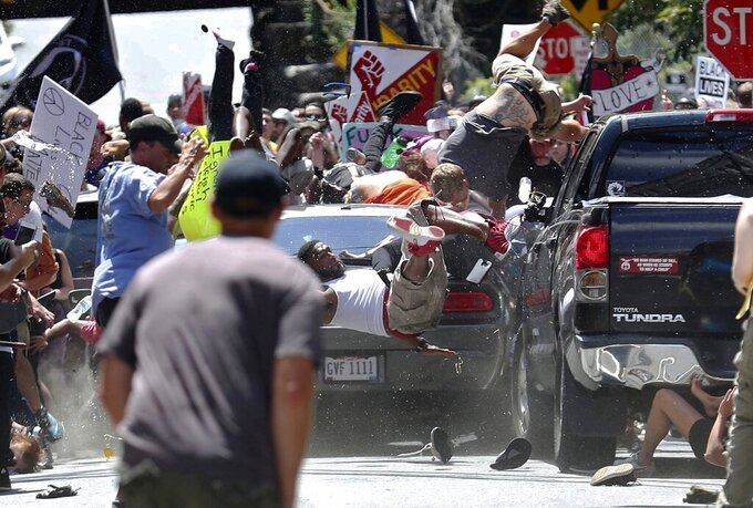 FILE - In this Aug. 12, 2017, file photo, people fly into the air as a vehicle is driven into a group of protesters demonstrating against a white nationalist rally in Charlottesville, Va. James Alex Fields Jr. Fields, who was sentenced to to life in prison on federal hate crime charges for deliberately driving his car into anti-racism protesters during a white nationalist rally in Virginia, is set to face a state judge on Monday, July 15, 2019, who could add another life sentence, plus 419 years.(Ryan M. Kelly/The Daily Progress via AP, File)