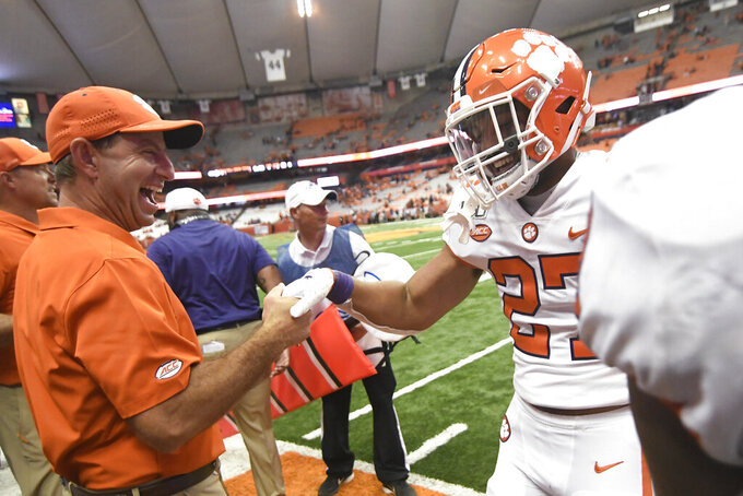 Clemson's Chez Mellusi celebrates a fourth-quarter touchdown against Syracuse with Clemson coach Dabo Swinney during an NCAA college football game Saturday, Sept. 14, 2019, in Syracuse, N.Y. (AP Photo/Steve Jacobs)