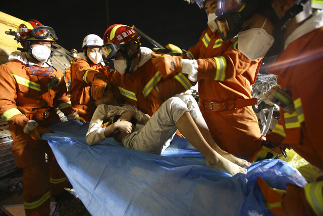 In this March 9, 2020 photo released by Xinhua News Agency, rescuers place a boy pulled from the rubbles of a collapsed hotel on a stretcher in Quanzhou, southeast China's Fujian Province. Several have been killed and others trapped when in the collapsed Chinese hotel that was being used to isolate people who had arrived from other parts of China hit hard by the coronavirus outbreak, authorities said Sunday. (Zeng Demeng/Xinhua via AP)