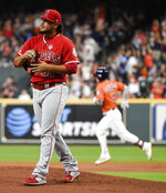 Los Angeles Angels starting pitcher Jaime Barria, left, walks off the mound as Houston Astros' Alex Bregman, back right, rounds the bases after hitting a solo home run during the first inning of a baseball game Friday, Sept. 20, 2019, in Houston. (AP Photo/Eric Christian Smith)