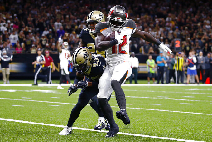 Tampa Bay Buccaneers wide receiver Chris Godwin (12) scores a touchdown against New Orleans Saints free safety Marcus Williams (43) and strong safety Vonn Bell (24) in the first half of an NFL football game in New Orleans, Sunday, Oct. 6, 2019. (AP Photo/Butch Dill)