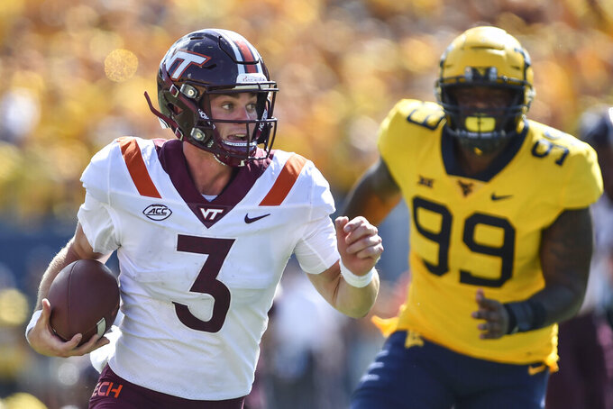 Virginia Tech quarterback Braxton Burmeister (3) rushes the ball against West Virginia during the second half of an NCAA college football game in Morgantown, W.Va., Saturday, Sep. 18, 2021. (AP Photo/William Wotring)