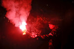 A man holds a flare as people take part in the