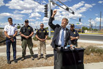 Albuquerque Mayor Tim Keller, accompanied by law enforcement officials, indicates the trajectory of the fatal balloon crash during a news conference in Albuquerque, N.M., Saturday, June 26, 2021. Police said five occupants of a hot air balloon died after they crashed on a busy street. (AP Photo/Andres Leighton)
