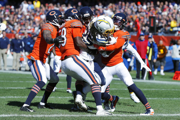 Los Angeles Chargers running back Melvin Gordon, center, scores on a 19-yard touchdown run during the first half of an NFL football game against the Chicago Bears, Sunday, Oct. 27, 2019, in Chicago. (AP Photo/Charles Rex Arbogast)
