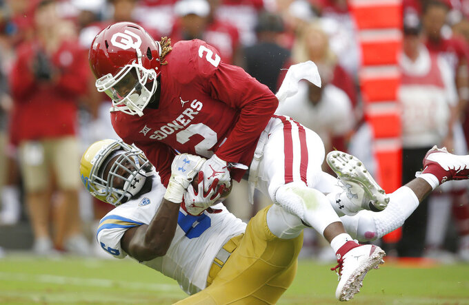 Oklahoma wide receiver CeeDee Lamb (2) catches a pass and is immediately tackled by UCLA defensive back Adarius Pickett (6) in the first quarter of an NCAA college football game in Norman, Okla., Saturday, Sept. 8, 2018. (AP Photo/Sue Ogrocki)
